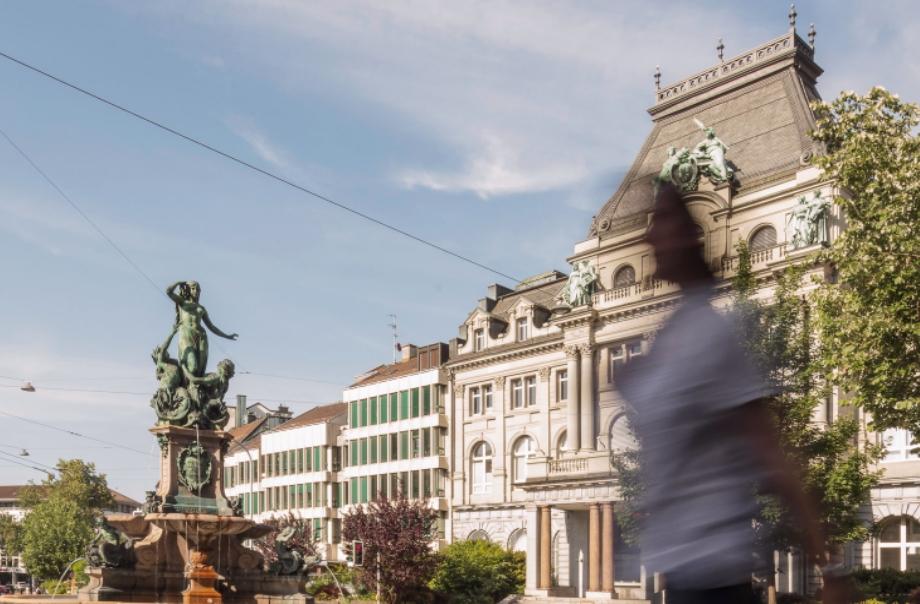 Innenstadt Häuserfasade, im Vordergrund unscharfe Person und Brunnen mit Statue