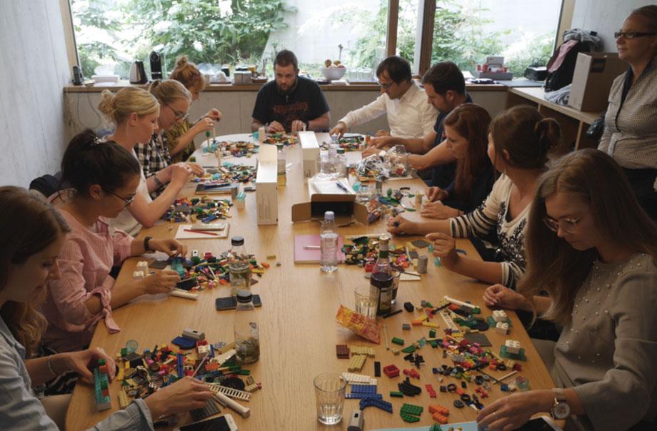 12 Personen sitzen um einen Tisch und bauen mit Legosteinen