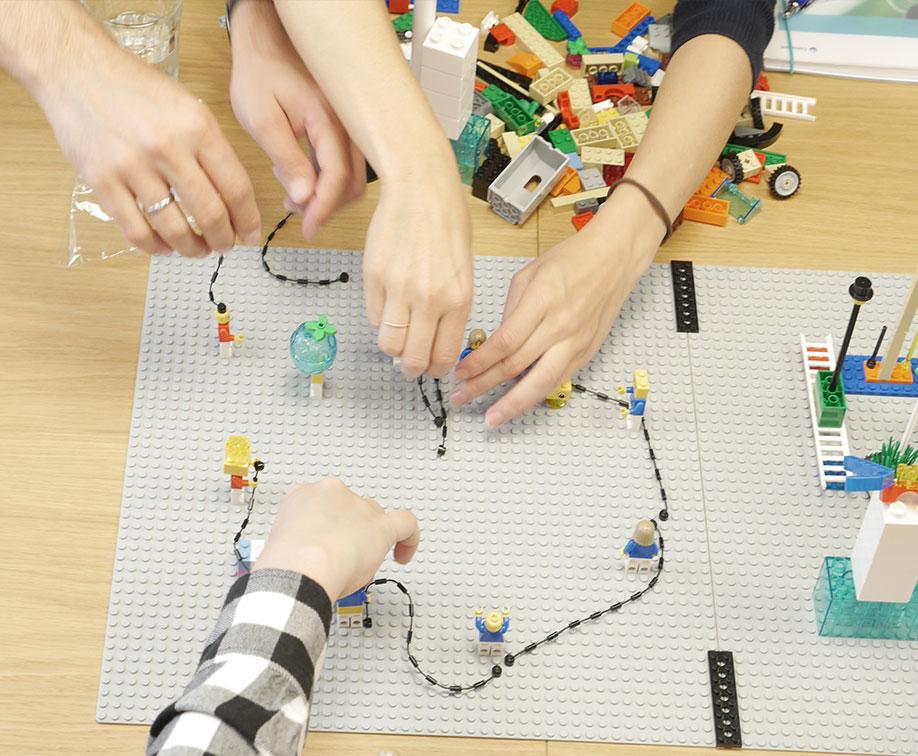 Nahaufnahme von 5 Händen welche eine Lego-Personen-Kette auf einer Lego Platte aufbauen.