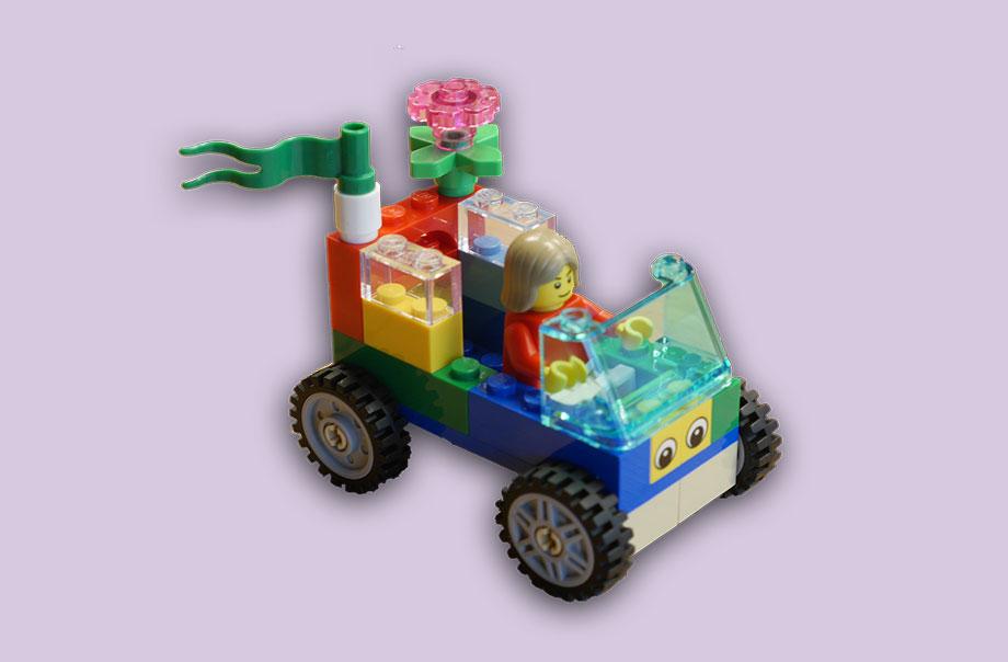 Selbstgebautes Lego Auto aus bunten Steinen mit einer Fahne, Blume und ohne Dach. Fahrzeuglenker mit langen braunen Haaren.