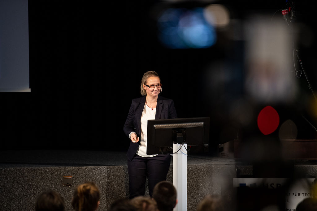 Susanne Schmidt-Rauch steht schmunzelnd auf der Bühne hält einen Vortrag.