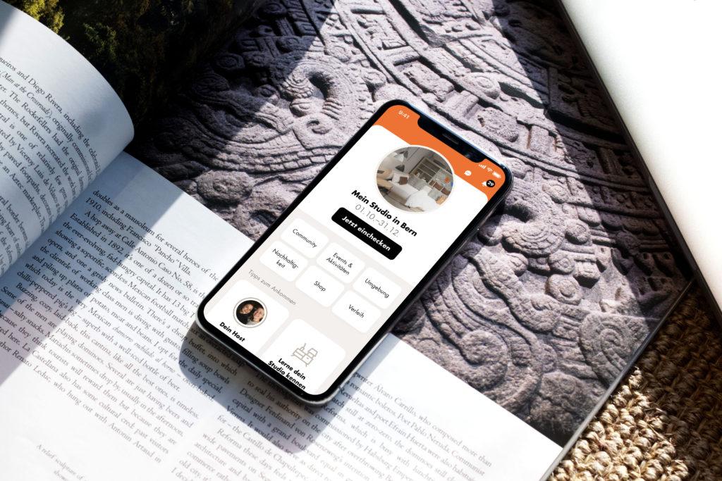 Handy mit Hotel App Screen in stimmungsvoller Umgebung platziert